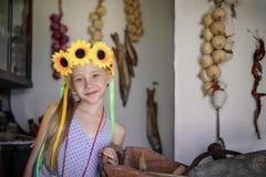 美丽的女孩用在头的向日葵在村庄小屋 图库摄影