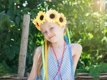 美丽的女孩用在头的向日葵在树前面的阳光下 库存图片
