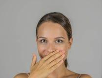 美丽的女孩用在她的嘴的手 库存图片