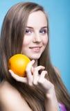 美丽的女孩用在蓝色背景的桔子 库存图片