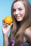 美丽的女孩用在蓝色背景的桔子 图库摄影