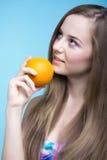 美丽的女孩用在蓝色背景的桔子 免版税图库摄影