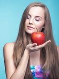 美丽的女孩用在蓝色背景的红色苹果 免版税库存图片