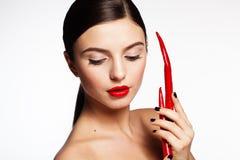 美丽的女孩用热的红辣椒 库存图片