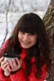 美丽的女孩用茶在冬天森林里 免版税库存图片