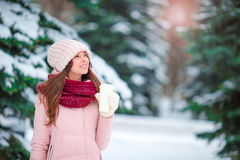 美丽的女孩用去的咖啡户外在美好的冬天雪天 免版税库存图片