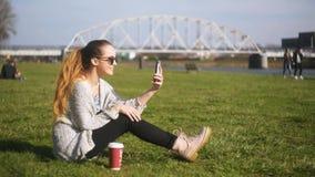 美丽的女孩由视频通信讲话谈话在电话 女孩笑,垂悬,微笑 分享impres的交换学生 影视素材