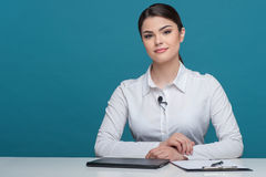 美丽的女孩电视新闻广播员报告坐 免版税库存图片