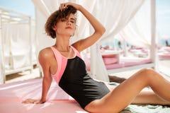 美丽的女孩画象坐在海滩帐篷和梦想看在照相机的时髦泳装的,当整理她时 免版税库存照片