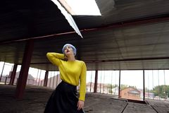 美丽的女孩画象有蓝色头发和红色嘴唇的在建造场所的一件黄色毛线衣 库存照片