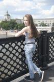 美丽的女孩画象桥梁蓝天背景的与在风的吹的头发 免版税库存照片