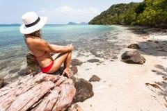 美丽的女孩白发和红色swimmingsuit坐岩石海滩,放松和享受自由 免版税库存照片