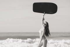 美丽的女孩的图片有bodyboard的,为乐趣准备 pink scallop seashell 免版税库存照片