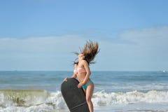 美丽的女孩的图片有bodyboard的,为乐趣准备 pink scallop seashell 库存图片