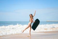 美丽的女孩的图片有bodyboard的,为乐趣准备 pink scallop seashell 免版税库存图片