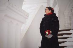 美丽的女孩的画象,新娘在降雪期间的冬天 免版税图库摄影