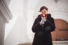 美丽的女孩的画象,新娘在降雪期间的冬天 免版税库存图片