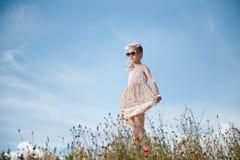 美丽的女孩短小穿礼服的和时髦太阳镜在夏天中调遣与花有蓝天背景 库存图片