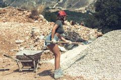 美丽的女孩短裤的, T恤杉和培养有石渣的红色被锐化的盖帽的一把铁锹 库存图片