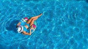 美丽的女孩空中顶视图从上面游泳池的,放松在可膨胀的圆环多福饼的游泳在家庭的水中 图库摄影