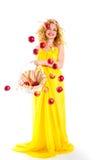 美丽的女孩穿戴的黄色用苹果 图库摄影