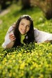美丽的女孩草愉快位于 免版税库存图片