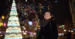 美丽的女孩获得在大肥皂泡中的乐趣在城市在晚上 库存图片