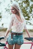 美丽的女孩行家自行车 库存照片