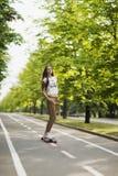 美丽的女孩行家T恤杉、短裤和运动鞋乘驾在轨道在公园longboard的 溜冰板运动 生活方式 免版税库存照片