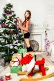 美丽的女孩装饰一棵圣诞树 免版税库存照片