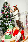 美丽的女孩装饰一棵圣诞树 免版税库存图片