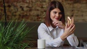 美丽的女孩谈话与使用一台手机照相机的商务伙伴 股票视频