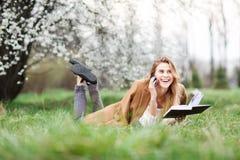 美丽的女孩谈话在她的电话在开花庭院里在一个春日 库存图片