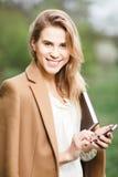 美丽的女孩谈话在她的电话在开花庭院里在一个春日 免版税库存照片
