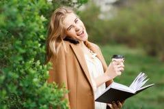 美丽的女孩谈话在她的电话在开花庭院里在一个春日 免版税库存图片