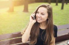 美丽的女孩谈话在电话晴天 图库摄影
