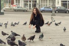 美丽的女孩蹲下来和喂养鸽子 免版税图库摄影