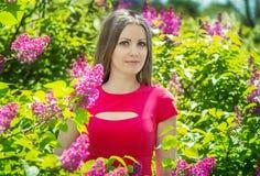 美丽的女孩近的开花的丁香 免版税库存照片
