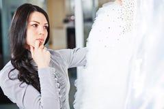 美丽的女孩选择她的婚礼礼服 画象在新娘sa中 免版税库存照片