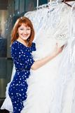 美丽的女孩选择她的婚礼礼服 画象在新娘sa中 免版税库存图片