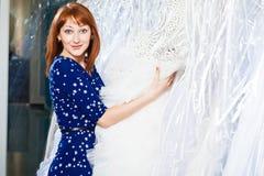美丽的女孩选择她的婚礼礼服 画象在新娘sa中 库存照片