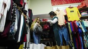 美丽的女孩选择并且对待袋子由在精品店的皮革制成 股票录像