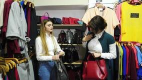 美丽的女孩选择并且对待袋子由在精品店的皮革制成 影视素材
