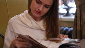 美丽的女孩选择菜单神色 免版税库存图片