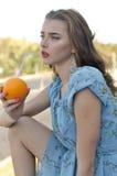 美丽的女孩通过从桔子的秸杆喝汁液 免版税库存图片