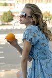 美丽的女孩通过从桔子的秸杆喝汁液 库存图片
