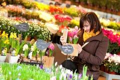 美丽的女孩采购的花在花市场上 库存图片