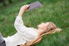 美丽的女孩阅读书在开花庭院里在一个春日 免版税库存图片