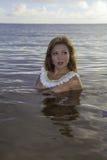 美丽的女孩露胸部在海洋 库存图片