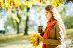 美丽的女孩食用咖啡在秋天公园 免版税库存图片